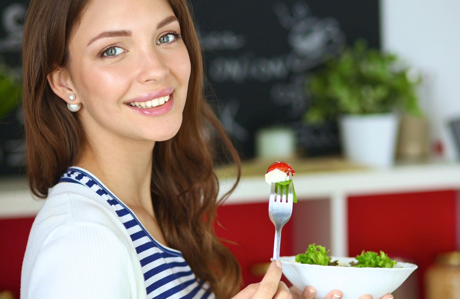 BM_Young woman eating salad and holding_95367192