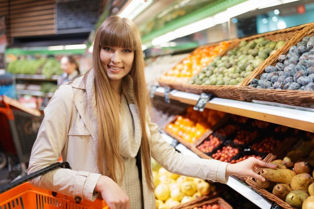 BM_Woman choosing fruits at supermarket and holding pear_97755676