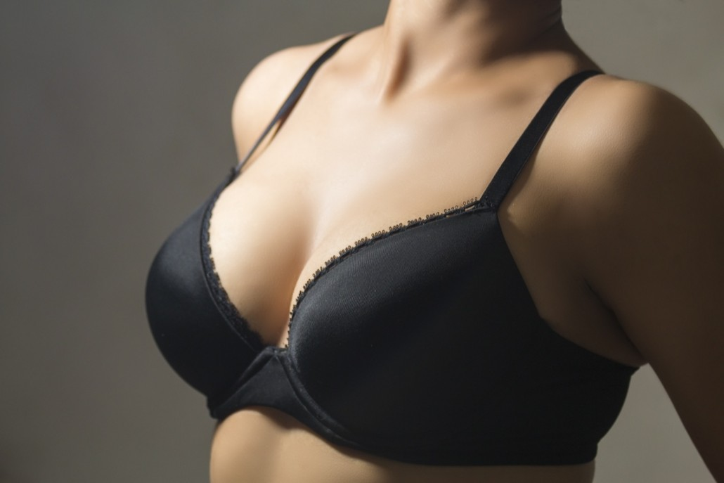 BM_Woman wearing a black brassiere isolated on a gray background_81369175