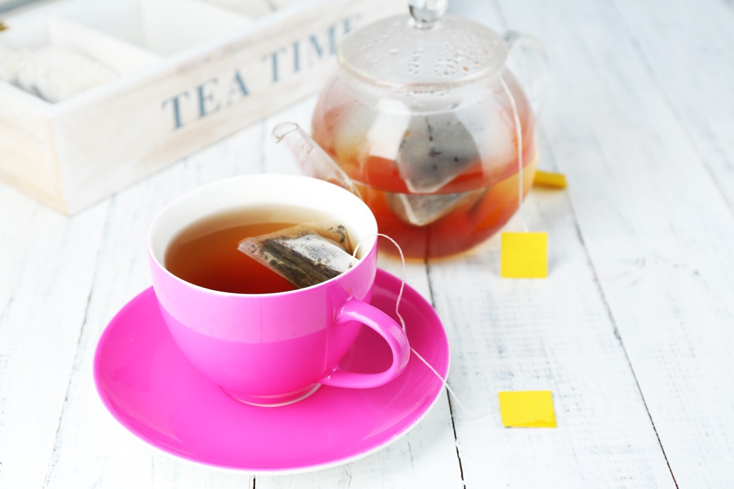 BM_Cup of tea, teapot and tea bags on wooden table close-up_70658662