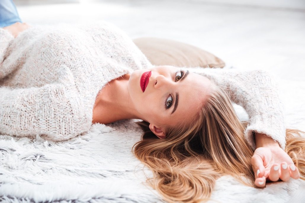 bm_attractive-woman-in-sweater-lying-on-the-carpet-at-home_126115999