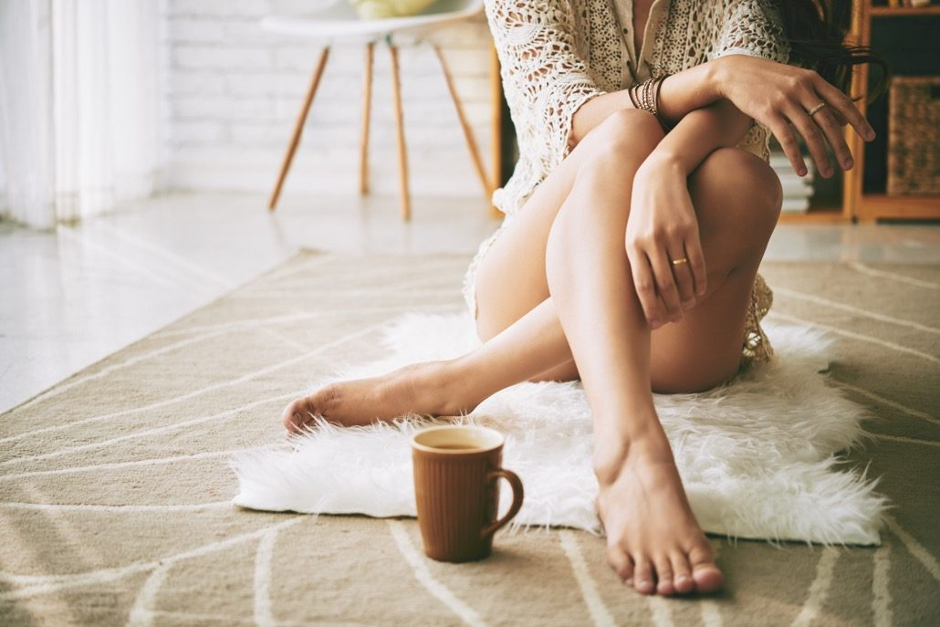 BM_Legs of woman sitting on the floor with cup of coffee_116795745