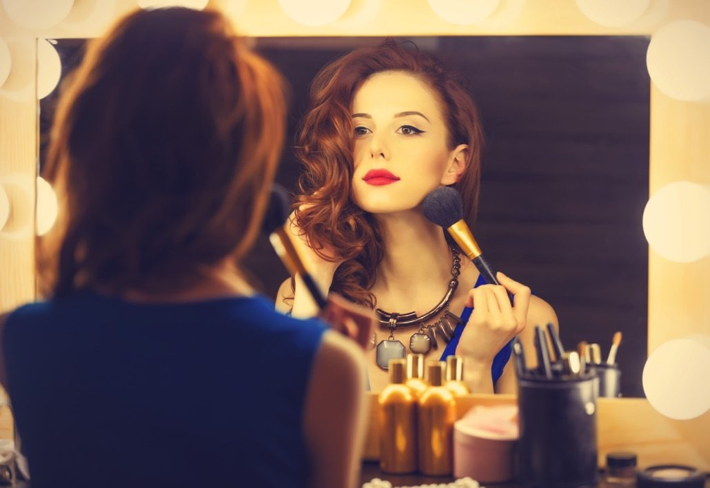 BM_Portrait of a beautiful woman as applying makeup near a mirror_75935787