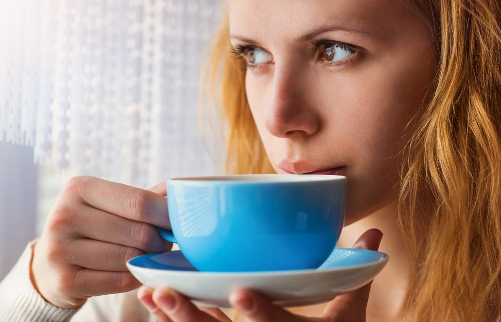 BM_Beautiful woman sipping coffee from her cup_81555486