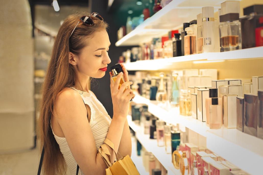 BM_Classy woman choosing a perfume inside a perfumery_85929931