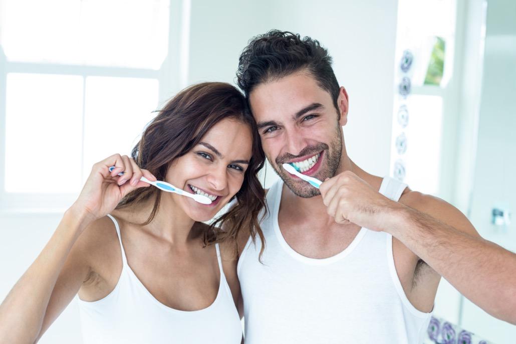 BM_Happy couple brushing teeth in bathroom_107925902