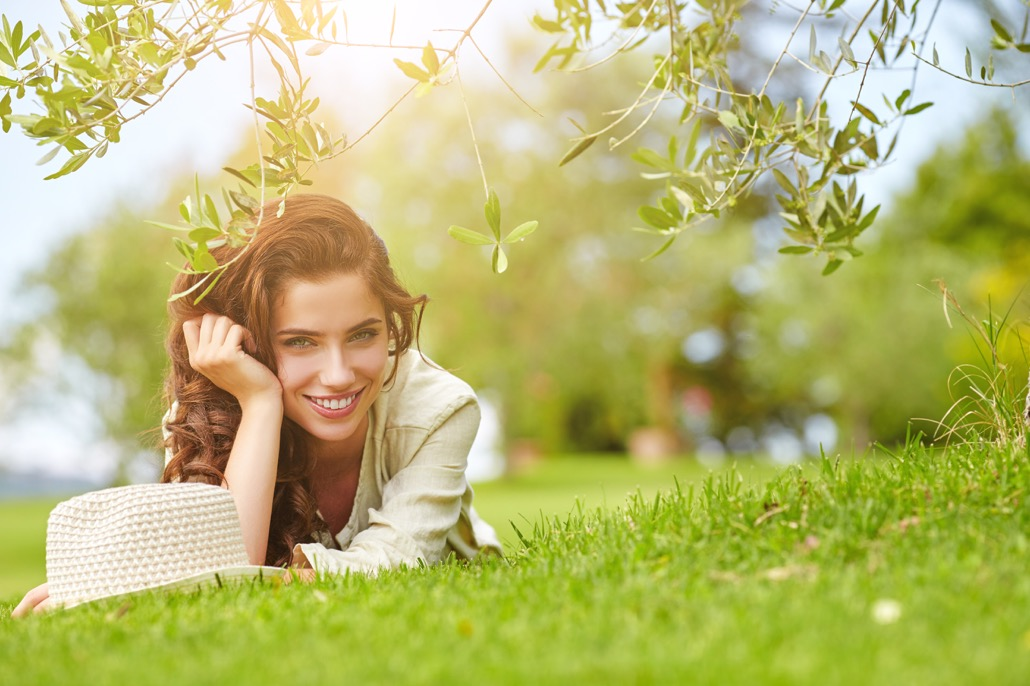 BM_Beautiful smiling woman lying on a grass outdoor_102316741