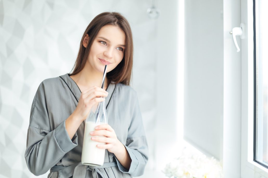 BM_Happy attractive young woman in grey bathrobe drinking milk_110761826