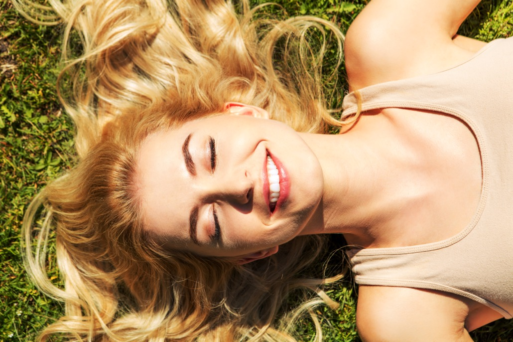 BM_Happy young woman lying on the grass_114945538