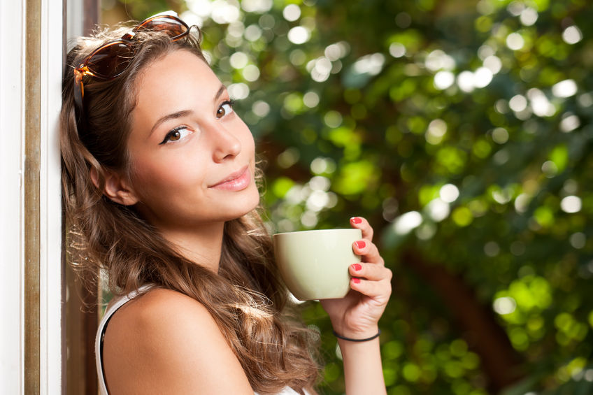 36826748 - smiling brunette beauty holding green cup with hot beverage.